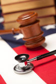Gavel, Stethoscope and Books on Flag — Stockfoto