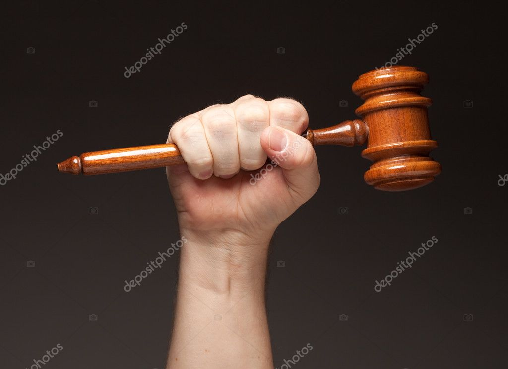 Male Fist Holding Wooden Gavel on a Grey Background.  Stock Photo #2328572