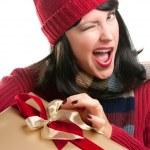 Подмигивающий женщина держит подарок к празднику — Стоковое фото