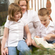 Young Boy Reads to His Mother and Sister — Stock Photo #2343713