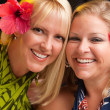 Two Smiling Girls with Hibiscus Flowers - Stock Photo