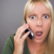 Stunned Blond Woman Using Cell Phone Aga — Stock Photo