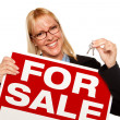 Woman Holding Keys and For Sale Sign — Stock Photo