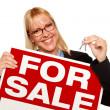 キーを保持している女性と売却の記号 — ストック写真