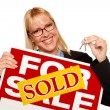 Woman Holding Keys Sold For Sale Sign — Stock Photo