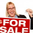 Woman Holding Keys and For Sale Sign - Stock Photo