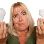 confundido rubia sostiene la bombilla de ahorro de energía — Foto de Stock