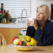 Stock Photo: Contemplative Woman in Kitchen with Mug
