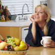 Woman Chats over Coffee in Kitchen - Zdjęcie stockowe