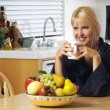 Stock Photo: Woman with Cup of Coffee in Kitchen