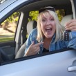 Stock Photo: Excited Girl In New Car with Keys