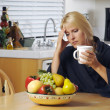 Stressed Woman Holding Head in Kitchen - Stockfoto