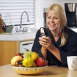 Happy Woman Texting in Kitchen - Stock Photo