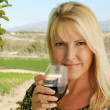 Attractive Girl Sips Wine at Vineyard - Stock Photo