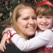 Mother and Child Hug in Front of Christmas Tree — Stock Photo