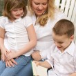 Young Boy Reads to His Mother and Sister — Stock Photo
