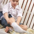 Stock Photo: Young Boy Getting Dressed Putting His Socks