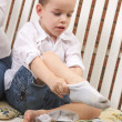 Stock Photo: Adorable Young Boy Getting Dressed Putting His Socks On