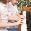 Brother and Sister Playing the Piano Together - Stock Photo