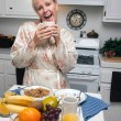 Attractive Woman In Kitchen with Fruit, Coffee, — Stock Photo
