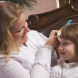 Foto Stock: Young Mother and Daughter Brushing hair