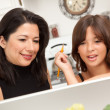 Hispanic Mother, Daughter Using Laptop - Stock Photo