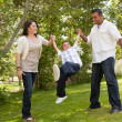 Hispanic Man, Woman and Child in Park - Stock Photo