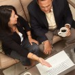 Foto Stock: Man and Woman Using Laptop with Coffee