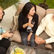 Three Friends Enjoying Wine on Patio - Stock Photo