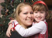 Mom and Child Hug by a Christmas Tree — Stock Photo