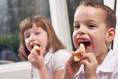 Zus en broer eten van een appel — Stockfoto