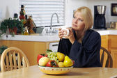 Contemplative Woman in Kitchen with Mug — Stock Photo