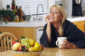 Woman Chats over Coffee in Kitchen — Stock Photo
