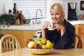Vrouw met kop koffie in keuken — Stockfoto