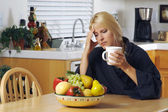 Stressed Woman Holding Head in Kitchen — Stock Photo