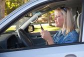 Vrouw voor sms-berichten tijdens het rijden — Stockfoto