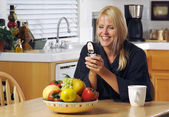 Happy Woman Texting in Kitchen — Stock Photo