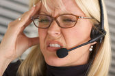 Woman with Phone Headset and Headache — Stock Photo