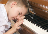 Young Boy with Head on Hand Playing the Piano — Stock Photo