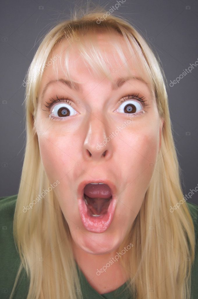 Shocked Blond Woman with Funny Face against a Grey Background  Stock Photo #2344464