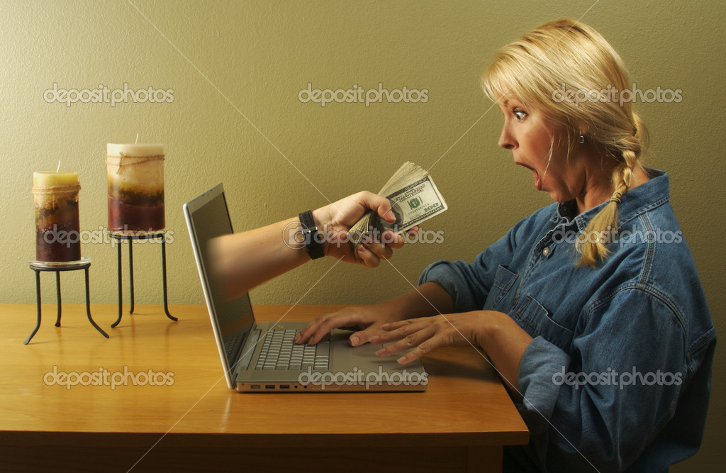 Attractive business woman shocked to see a hand coming through her laptop screen handing her lots of money. Can it be that simple? — Foto Stock #2345141