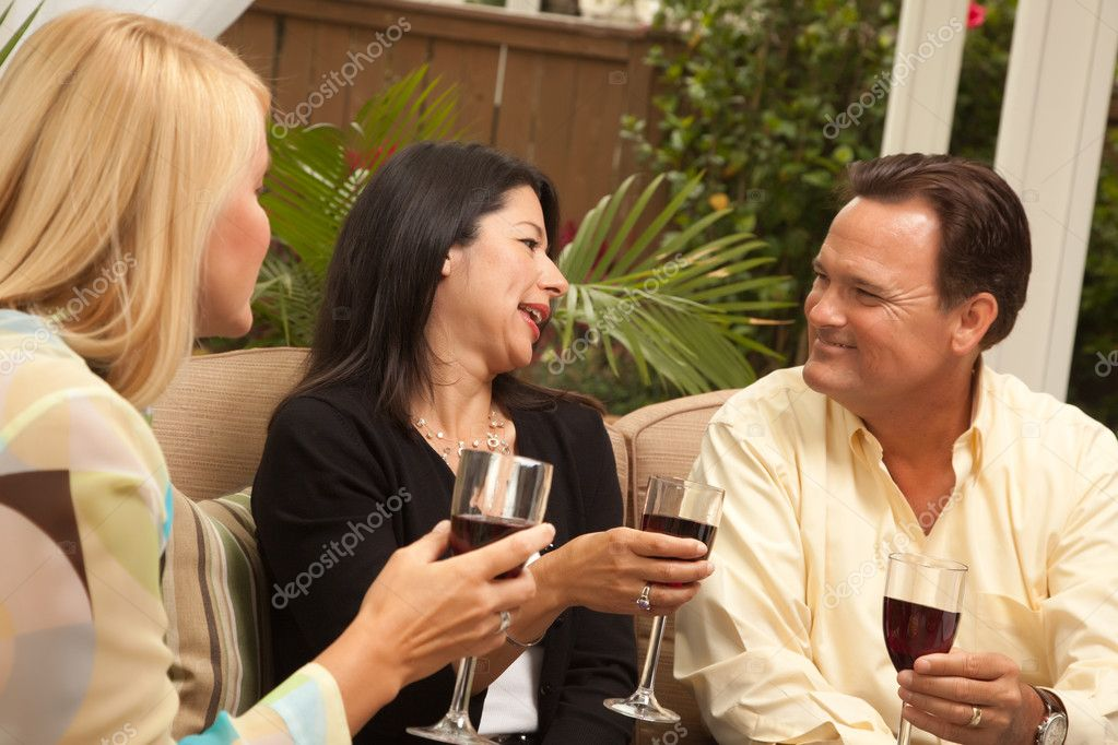 Three Friends Enjoying Wine on an Outdoor Patio.  Stock Photo #2349738