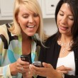 Two Girlfriends Sharing with Cell Phones — Stock Photo #2350102