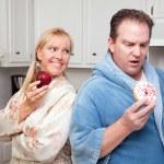pár v kuchyni s ovocem a koblihy — Stock fotografie