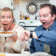 Stressed Couple Eating, Looking at Time - Stock Photo
