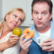 Couple in Kitchen with Fruit and Donuts - Stockfoto