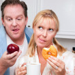 couple in kitchen with fruit and donuts — Stock Photo #2354652