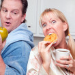 Couple in Kitchen with Fruit and Donuts — Stock Photo #2354707