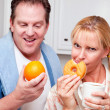 Couple in Kitchen with Fruit and Donuts - Foto Stock