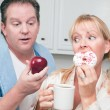 Couple in Kitchen Eating Donut vs Fruit — Stock Photo